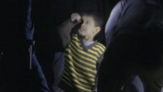 A child in a striped top is surrounded on all sides by uniformed police that he is only waist-high to in this night-time photograph