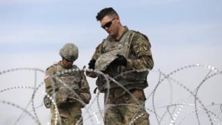 Dois soldados fardados olham para seus equipamentos com ar compenetrado, atrás de uma cerca de arame farpado