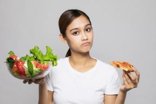Una mujer joven sosteniendo una ensalada en una mano y en la otra un trozo de pizza.