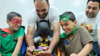 Charity workers with boys dressed as superheroes