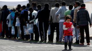 göçmenler italyada sıraya girmiş