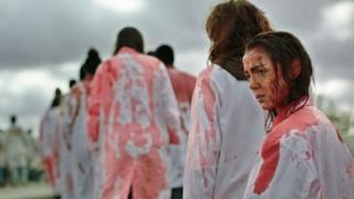 Un fotograma de la película que muestra a la protagonista con la cara llena de sangre y una bata blanca salpicada también de sangre haciendo una fila detrás de otras personas.