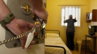 Prison officer locking a cell door