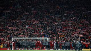 Liverpool players and staff celebrating the Champions League semi-final win against Barcelona with fans in the Kop