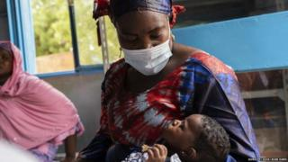 Rafatou holds her son while waiting for him to be vaccinated, at Gamkalé health centre, Niger