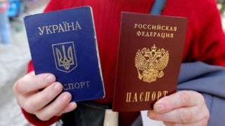 A woman poses with her Ukrainian passport (blue) and new Russian passport (red) in Simferopol, Crimea, 7 April 2014