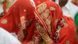 سيدات هنديات يلبسن الزي التقليدي وقد غطين وجوههن