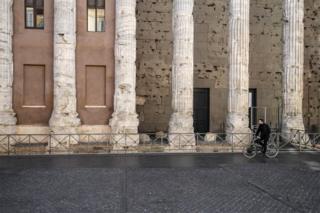 A man rides a bike past ancient stone columns