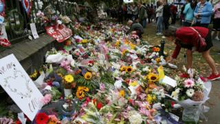 Residents look at flowers in tribute to victims in Christchurch on 18 March
