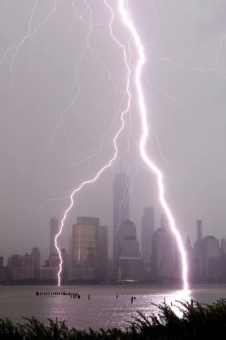 Lightning bolts hit a river with a city skyline behind