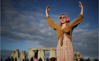 Жінка зустрічає сонце біля Стоунхенджу
