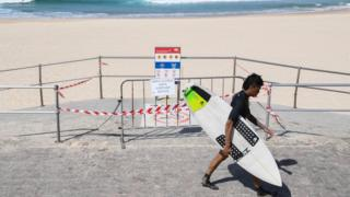 A surfer walks past Bondi Beach which is closed due to coronavirus restrictions