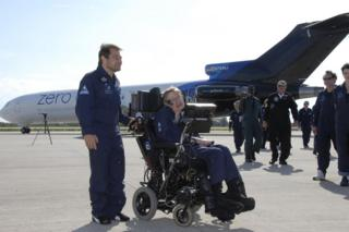 Stephen Hawking waits next to a plane