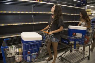 University of Hawaii at Manoa students push trolleys around a supermarket.