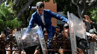 Juan Guaidó tries to gain access to the National Assembly building as National Guard members push him back