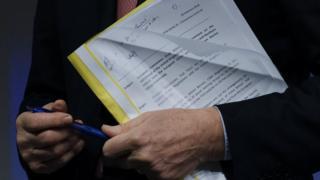 Michel Barnier holding the EU draft withdrawal agreement document in a plastic folder
