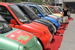 An Indian woman passing a line of electric Reva Motorcars before a Reva car rally is thought to celebrate the world day in New Delhi on June 5, 2009.
