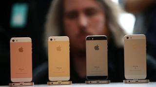 iPhones on display with man in background