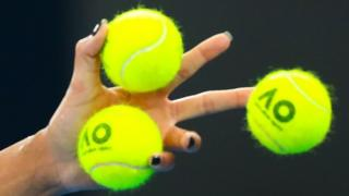 A close-up of three tennis balls in Madison Keys' hand.