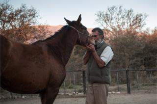 Oscar con un caballo salvaje.