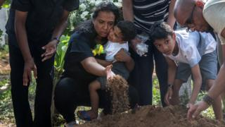 "A woman holds a crying child as she throws earth onto a coffin during a funeral for a person killed in the Easter Sunday attack on St Sebastian""s Church, on April 23, 2019 in Negombo"