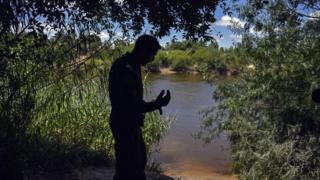 United States Border Patrol agent Robert Rodriquez looks across the Rio Grande into Reynosa, Mexico,