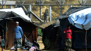 A Myanmar security personnel keeps watch along the Myanmar-Bangladesh border as Rohingya refugee stand outside their makeshifts shelters near Tombru, in the Bangladeshi district of Bandarban on 1 March 2018.