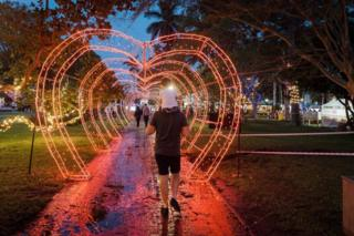 in_pictures People walk through a heart-shaped tunnel of red Christmas lights.