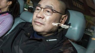 Joseph Lau Luen-hung leaves a restaurant with a girlfriend in Hong Kong March 17, 2014
