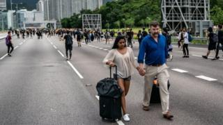 Passengers with their luggage walk to Hong Kong's airport. Photo: 1 September 2019