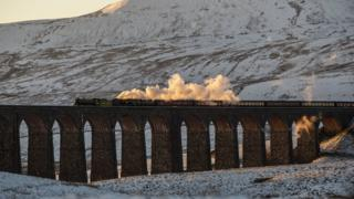 A train crosses the Ribblehead Viaduct amid wintry scenes in North Yorkshire.