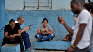 cep telefonlarına bakan Kübalılar