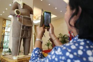 A Cambodian takes a picture of a Khmer statue on display during a ceremony in Phnom Penh, Cambodia, 28 March 2016