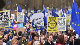 Protesters hold a placard showing a picture of Boris Johnson with the words 'All about me not EU' during the Put It To The People March on March 23, 2019 in London, England.