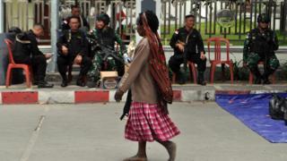 Warga melintasi penjagaan prajurit TNI dan Polri di Wamena,Papua, Sabtu (30/11).