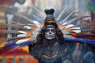 A participant holds up a censer during the annual Day of the Dead parade in Mexico City
