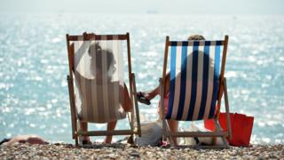 Two people sit in deckchairs