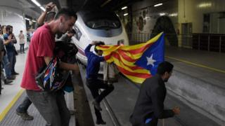 Protesters carrying a pro-independence Catalan Estelada flag jump on tracks to block trains at the Sants Station in Barcelona during a strike called by a pro-independence union in Catalonia on November 8, 2017.