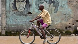 "A man on a bike drives past a wall with portraits of Argentine-born guerrilla leader Ernesto ""Che"" Guevara (1928-1967) (L) and former Libyan dictator Muammar Gaddafi (1942-2011) in a quarter of Abidjan on November 14, 2017."