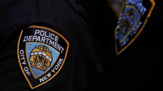 A New York Police Department badge on an officer's uniform