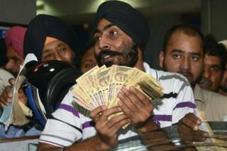 Indian bank customers wait to deposit 500 and 1,000 rupee notes at a bank in Amritsar on November 10, 2016