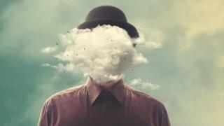 A surreal picture of a man in a bowler hat with a big white cloud instead of his head