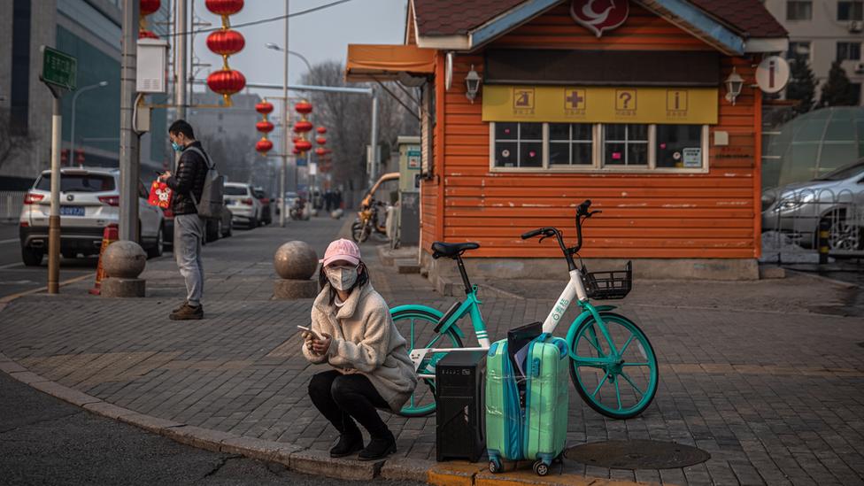 Женщина сидит у сумок на обочине дороги в Пекине
