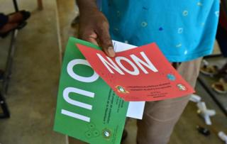 A man holds ballots before voting for a referendum on a new constitution on October 30, 2016 at a polling station in Yopougon, suburb of Abidjan