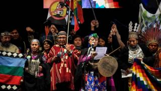 Members of indigenous communities speak onstage after a mass climate march