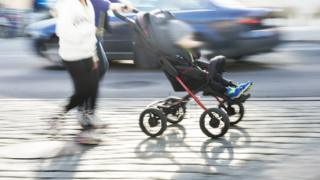 Pushing a pram along a busy road