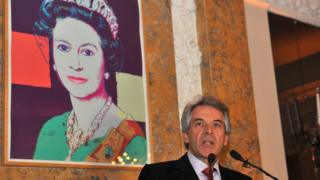 Sir Peter Westmacott, British ambassador to the US, speaks in front of an Andy Warhol portrait of the Queen