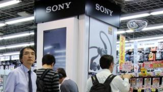 Customers check Japanese electronics giant Sony's headphones at an electronics shop in Tokyo on 30 April 2015