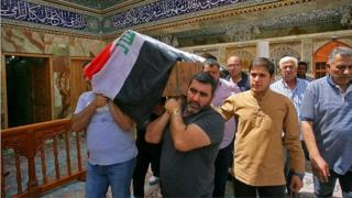 Mourners carry the coffin of a victim of bombing in Baghdad