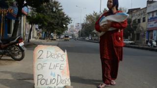 A woman walks to a polio vaccine camp with her baby